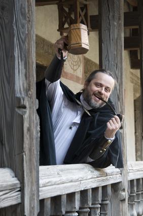 Ritter prostet mit Weinkrug und Tabakpfeife im Mund
